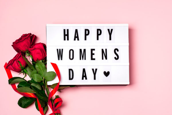 Happy women's day inscription on the lightbox, red roses with red ribbon on the pink background. 8 march concept. Top view, flat lay composition.